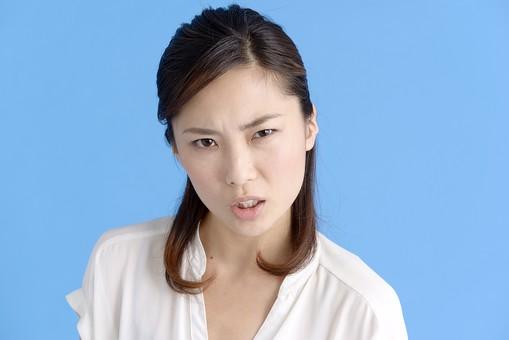 女性 ポーズ 人物 30代 日本人 黒髪 爽やか カジュアル 屋内 正面 ブルーバック 青背景 半そで 白  怒り 怒る 非難 叱る 憤慨 腹立たしい 睨む 睨み付ける 上半身 激怒 凝視 疑い 疑問視 押えつける mdjf013