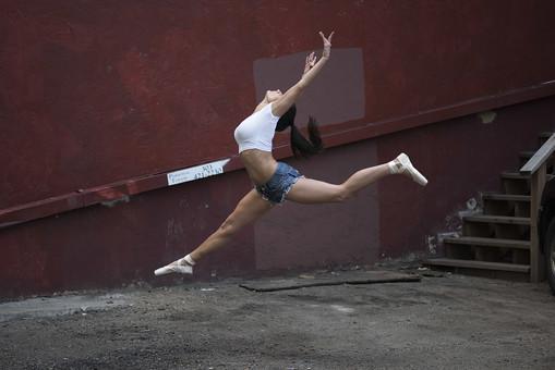 外国人 女性 おんな レディ 大人 ダンサー 黒髪 長髪 ロングヘア ストレートヘア ポニーテール 白シャツ ショートパンツ デニム トウシューズ バレエ ダンス ジャンプ ポーズ モーション 跳ねる 飛ぶ 浮かぶ 開く 伸ばす 束ねる 躍動 跳躍 開脚 均整 大胆 鍛練 筋肉 しなやか ボディ ライン 全身 側面 空中 瞬間 屋外 野外 中庭 パティオ 広場 路地 階段 壁 赤茶色 日中 日光 mdff024
