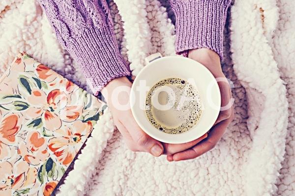 毛布の上でコーヒーを持つ手8の写真