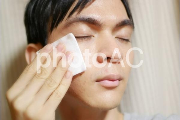 コットンで顔を拭く男性②の写真