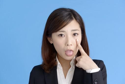 人物 女性 日本人 20代 若者  ビジネス スーツ 黒 紺色 セミロング  OL 社会人 会社員 ビジネスマン 就活  就職活動 真面目 ポーズ 屋内 スタジオ撮影  ブルーバック 上半身 正面 表情 舌を出す あっかんべー 人差し指 指 目 指す mdjf013