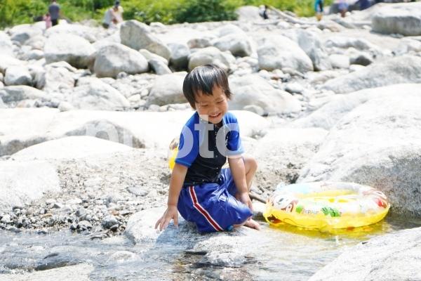 川で水遊びをする子供の写真