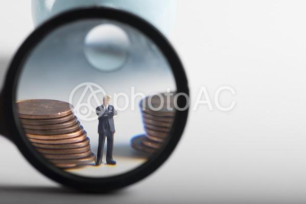 拡大鏡で見るビジネスマンのミニチュアと硬貨の写真