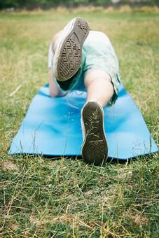 男性 男 足上げ 片足 足 後ろ 後ろ姿 筋肉 筋トレ トレーニング フィットネス 腹筋 ダイエット 芝生 ヨガマット マット 青マット 青 白 白シャツ 緑 エクササイズ セルフトレーニング 庭 野外 屋外 庭園 外国人 外人 20代 30代 ボディ ボディパーツ