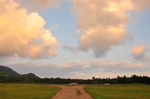 外国 海外 アジア 東南アジア フィリピン 熱帯 屋外 野外 自然 風景 景色 草原 野原 草野 丘 植物 草 芝 空 陽光 雲 積乱雲 彩雲 薄明 道 道路 牧場 ファーム 滑走路脇 路肩 広い 広大