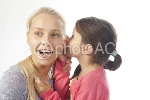 母親に耳打ちする娘3の写真