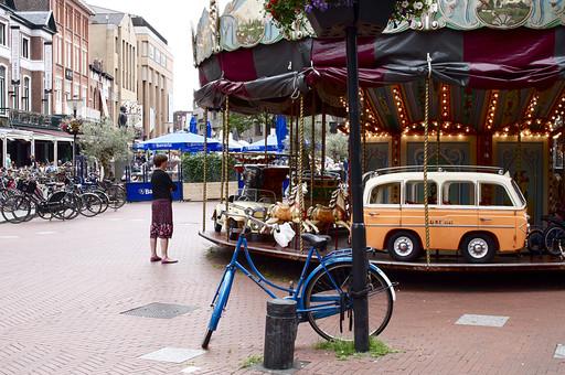 オランダ Holland アムステルダム 街並み 町 通り ストリート メリーゴーランド 遊具 車 回る メルヘン 自転車 のどか 街中 ユニーク 観光地 満車 駐輪場 建物 オシャレ 男の子 BOY  街角 海外 外国 異国の地