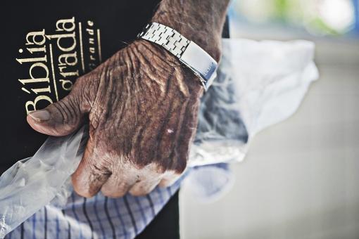 人物 老人 お年寄り 高齢者 シルバー 男性 おじいさん おじいちゃん 年老いた手 ハンドパーツ 手 指 ハンド パーツ 手の表情 クローズアップ 時計 腕時計 本 持つ 持ち歩く しわ シワ 皺 片手 手元 手先 指先