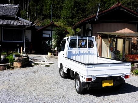 軽トラック 軽トラ トラック 白 ホワイト 荷台 作業車 砂利 じゃり ジャリ 石 小石 庭 ガーデン 晴天 晴れ 屋外 縦 後ろ バック 引き