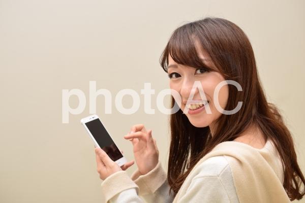 スマホを操作して笑顔の女性の写真