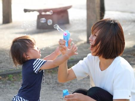 シャボン玉で遊ぶ女性と子供の写真