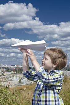 人物 外国人 子供 男の子 幼い 一人 紙 飛行機 紙飛行機 工作 作る 折る 作品 飛ぶ 飛ばす 遊ぶ 投げる つまむ 視線 狙う ポーズ 自然 空 雲 青 白 青空 晴天 天気 晴れ 草 緑 植物 町並み 野草 雑草 草原 原っぱ 葉 mdmk014