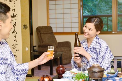 屋内 人物 日本人 2人  大人 男性 女性  20代 30代 夫婦 カップル 温泉施設 宿泊施設 ホテル 旅館 旅行 温泉 浴衣 ゆかた 和服 食事 飲食 食べ物 日本料理 和食 料理 座卓 ビール 持つ 座る 飲物 和室 畳 和風 どうぞ 楽しい 注ぐ 手を添える お疲れさま ねぎらう お願い いかが お酌 mdjm001 mdjf013