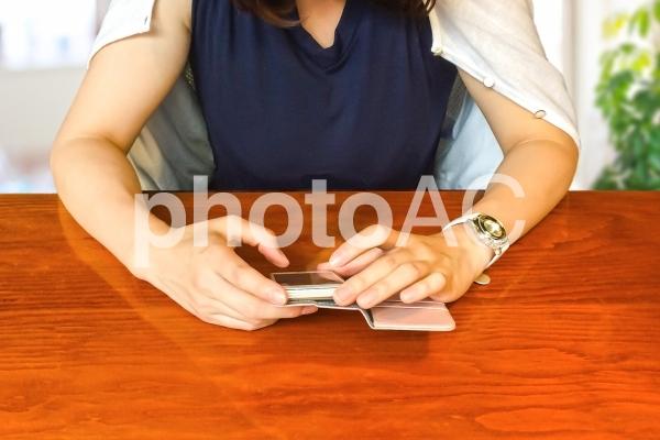 スマホをいじる女性の写真