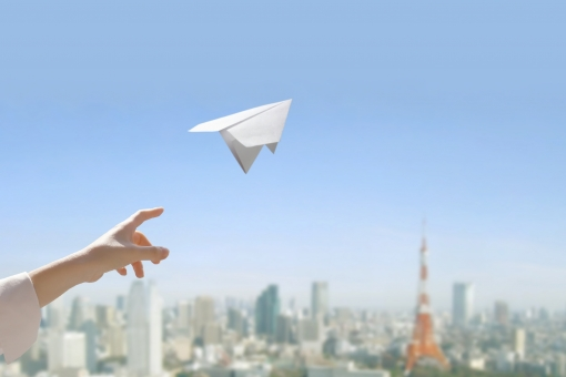 紙飛行機を飛ばす人の写真