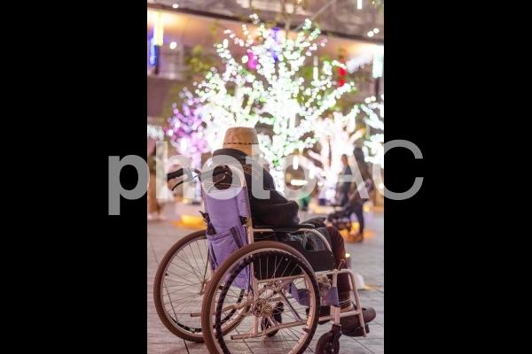 車椅子に乗ってイルミネーションを見ているシニア女性の写真