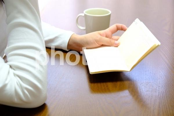 通帳を眺める女性(頬杖しながら)の写真