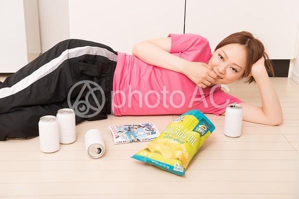横になってお菓子を食べる女性の写真