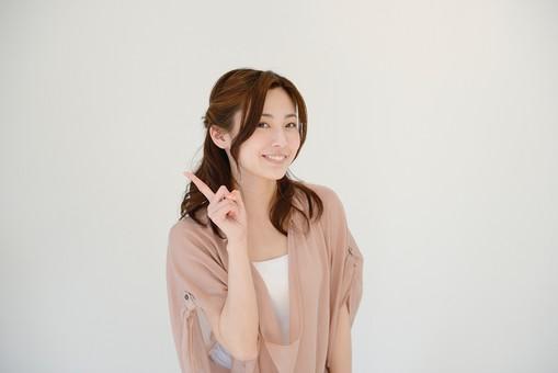 日本人 女性 女 30代 アラサー グレーバック 背景 グレー ポーズ ハーフアップ 髪型 茶髪 ナチュラル 私服 カジュアル ピンク ピンクベージュ 前のめり ポイント コツ 重要 人差し指 指 笑顔 スマイル サイン ジェスチャー mdjf013