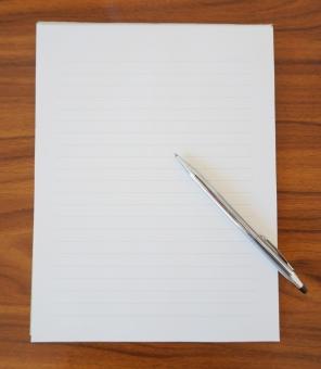 机の上の便せんとペンの写真