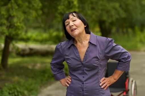屋外 野外 外 病院 庭 公園 外国人 老人 高齢者 女性 おばあさん おばあちゃん 患者 車椅子 車いす 立ち上がる 立つ 腰に手をやる 腰痛 腰を持つ やれやれ 疲れる 疲労 腰を揉む 腰に手を当てる 休憩 仁王立ち mdfs016