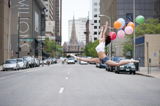 外国人 女性 おんな レディ 大人 ダンサー 黒髪 長髪 ロングヘア ストレートヘア 白シャツ ショートパンツ デニム トウシューズ バレエ ダンス ジャンプ モーション 跳ねる 飛ぶ 浮かぶ 横向き 開脚 伸ばす 風船 カラフル リボン 持つ 握る 横断 躍動 跳躍 全身 空中 瞬間 屋外 野外 街並 通り 道路 ストリート アスファルト 白線 ビル街 尖塔 教会 自動車 自転車 日中 mdff024