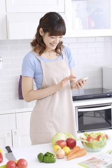 人物 屋内 日本人 1人 女性 20代 30代 キッチン 台所 準備 料理 調理 作る クッキング 生鮮野菜 材料 エプロン 野菜 ボウル サラダ 飾る  奥さん 奥様 婦人 家庭人 夫人 主婦 若い 家庭 家庭的 携帯 スマホ スマートフォン 見る 探す レシピ 持つ 指 滑らせる スワイプ タップ 下を向く mdjf018