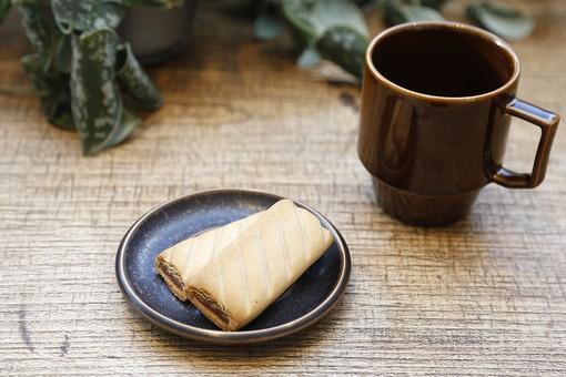 コーヒー 珈琲 カフェ コーヒーカップ カップ コップ マグカップ 茶色 テーブル 木製 木目 ビスケット クッキー 2枚 2つ 洋菓子 菓子 焼き菓子 皿 観葉植物 植物 葉 屋内 室内 部屋 コーヒータイム