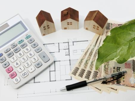 家の見積もりと観葉植物-計算機と積み木と設計図の写真