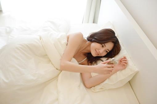 日本人 女性 女 30代 アラサー ライフスタイル 部屋 ベッドルーム 寝室 室内 ポーズ キャミ キャミソール 部屋着 ナチュラル ミディアムヘア ベッド 布団  朝 早朝 モーニング ゆっくり 休日 休み スマホ スマートホン 寝転んで 横になって mdjf013