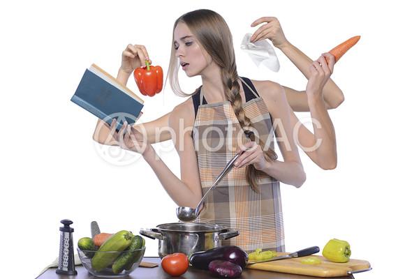 料理に忙しい女性の写真