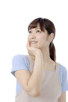 人物 屋内 白バック 白背景 日本人 1人 女性 20代 30代 エプロン  奥さん 奥様 婦人 家庭人 夫人 主婦 若い ポーズ 顔 表情 手 顎 あご 当てる 手を顎に当てる うれしい 嬉しい 喜び 喜ぶ 予感 幸運 ラッキー 希望 展望 mdjf018