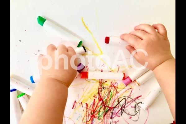 クレヨンで遊ぶ子供の手の写真
