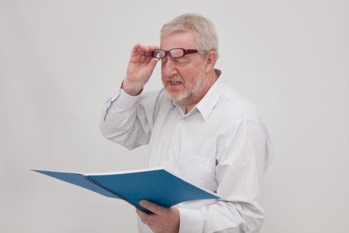 シニア 外国人 正面 ひげ 髭 上半身 髭面 白髪 シャツ 一人 初老 白背景 室内 ノート 青 ブルー 目を落とす 見る 見えない 眼鏡 メガネ 外す よく見る 困る 読めない 老眼 手をやる 上げる 1冊 男性 老眼 mdjms002