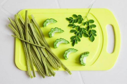植物 自然 野菜 アンパラヤ ゴーヤ 苦い フィリピン 熱帯 栄養 マルンガイ カモンガイ 健康 安価 緑 まな板 台所 料理 食事 キッチン ベジタブル 並べる 白背景 切る 準備 食材 食べ物