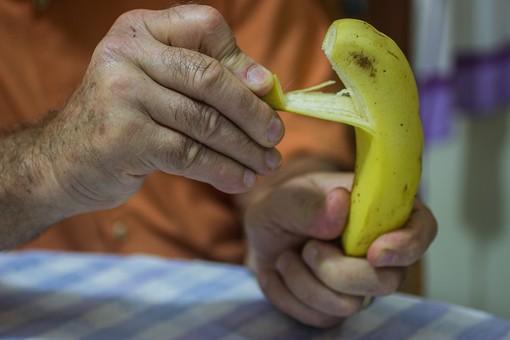 人物 老人 お年寄り 高齢者 シルバー  年老いた手 ハンドパーツ 手 指 ハンド  パーツ 手の表情 年老いた手 皺 しわ  シワ クローズアップ 食べ物 果物 フルーツ バナナ 皮 むく 剥く 食べる リハビリ 訓練 医療 福祉 手元 手先 指先