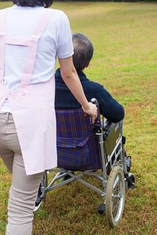 老人 高齢者 お年寄り シニア 男性 男 おとこ  2人 二人  介護士 看護師 エプロン  介護 不自由 椅子 ヘルパー 屋外 緑 木々 木 ジャケット ズボン 青  車いす 車椅子    座る  握る 手 押す 歩く 芝生 全身 後ろ姿 散歩 外出 mdjf017 mdjms004