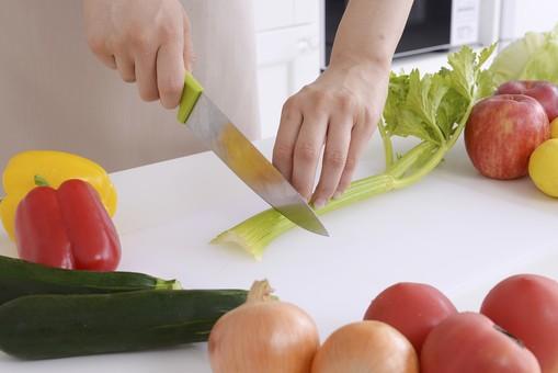 人物 屋内 日本人 1人 女性 手元 手 アップ 顔無し キッチン 台所 包丁 ナイフ 持つ 切る 切れる スライス カット 準備 料理 クッキング 生鮮野菜 材料 野菜 並ぶ セロリ パプリカ ズッキーニ 玉ねぎ トマト 新鮮 フレッシュ みずみずしい 調理 手を添える