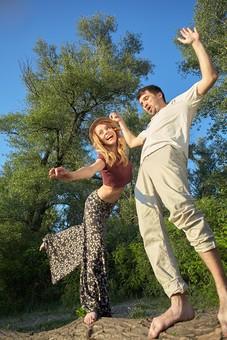 人物 外国人 外人 カップル 恋人  夫婦 男女 2人 大人 モデル  ポーズ 屋外 野外 自然  グリーン ファッション Tシャツ ラフ カジュアル  田舎 カントリー ラブラブ ハッピー 幸せ  仲良し 全身 空 青空 木 両手 手を広げる バランス 笑顔 支える 丸太 mdfm060 mdff104