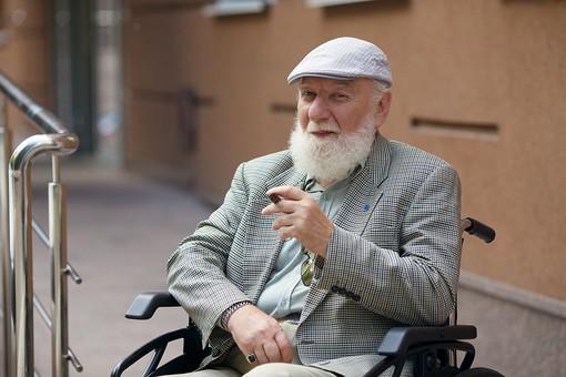 病院 医院 診療所 屋外 外 外国人 白人 男性 老人 高齢 高齢者 おじいさん おじいちゃん 髭 ヒゲ ひげ 白髪 車椅子 車いす 座る 乗る 乗せる 上着 ジャケット ハンチング帽 上半身 カメラ目線 たばこ タバコ 煙草 葉巻 葉巻き 吸う mdjms016