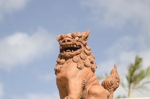 日本 国内 九州 沖縄県 屋外 空 雲 晴れ シーサー 置物 飾りもの 焼き物 茶色 動物 どうぶつ 獅子 魔除け 災い 素焼き 見上げる アップ 顔 風景 琉球 ユーモラス