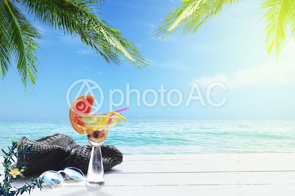 飲み物と帽子とサングラスが置いてある海辺のリゾートの写真