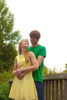 人物 外国人 外人 男性 女性 カップル 恋人 夫婦 2人 屋外 野外 外 自然 緑 グリーン 公園 手すり 柵 休日 デート 寄り添う 肩を寄せる 笑顔 スマイル 仲良し 散策 楽しい 幸せ 見つめ合う 見つめる 抱き寄せる mdff084 mdfm051