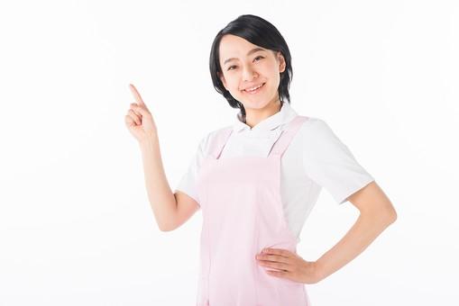 女性 おんな 女 エプロン 白衣 ピンク  介護 介護士 介助 ナース 病院  ヘルパー 看護師  手 指す 人差し指 人差指 ニコニコ 指 白 白背景 白バック 爽やか 優しい 穏やか 腕 腰 笑顔 スマイル mdjf017
