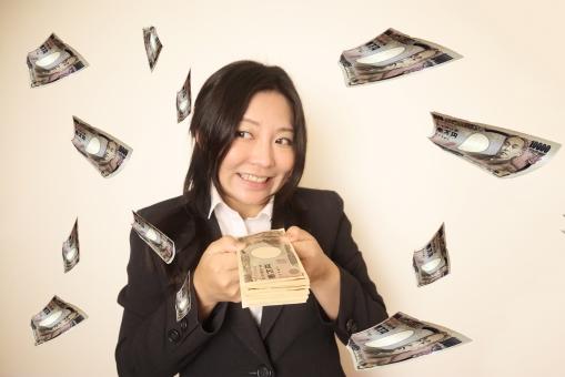 一万円札の束を持つスーツの女性の写真