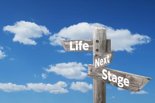 新たな人生とステージを示す木製道しるべと青空の写真