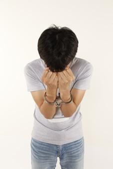 人物 男性 若者 手 手錠 犯罪 犯人 犯罪者 逮捕 検挙 事件 窃盗 詐欺 傷害 罪 現行犯 容疑者 捕まえる 正面 白バック 白背景 アップ Tシャツ ジーパン ジーンズ 上半身 顔を隠す 後悔 違法行為 不法行為 捕まる
