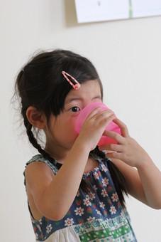 子供 人物 女の子 小学生 ジュース お茶 飲む 日本人 女子 少女 こども キッズモデル 正面 室内 屋内 白バック 白背景 上半身 コップ 飲み物 ドリンク おやつ 休憩 保育園 幼稚園 三つ編み あどけない かわいい mdfk034