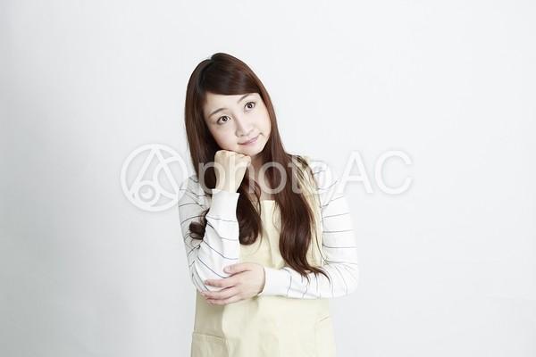 頬に手を置いて考える女性の写真