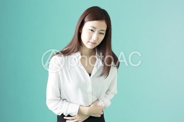 お腹が痛い女性の写真